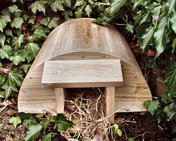 A wooden hedgehog house in a garden