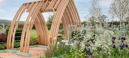 A wooden structure sitting in front of a flower garden