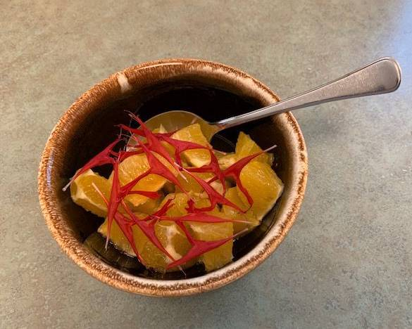 Thai basil syrup drizzled over cut up orange in a bowl