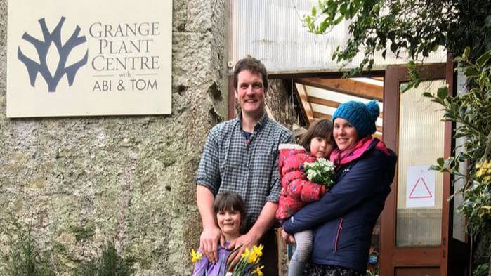 Abi and Tom standing with their children in front of their plant centre