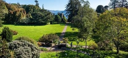 A large green field at Armadale Castle and Gardens with trees in the background