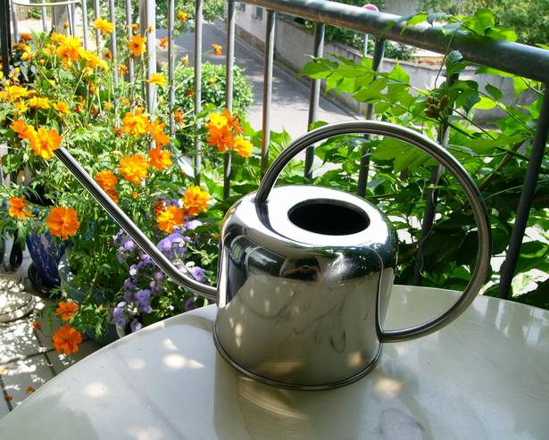 A metal watering can on a table