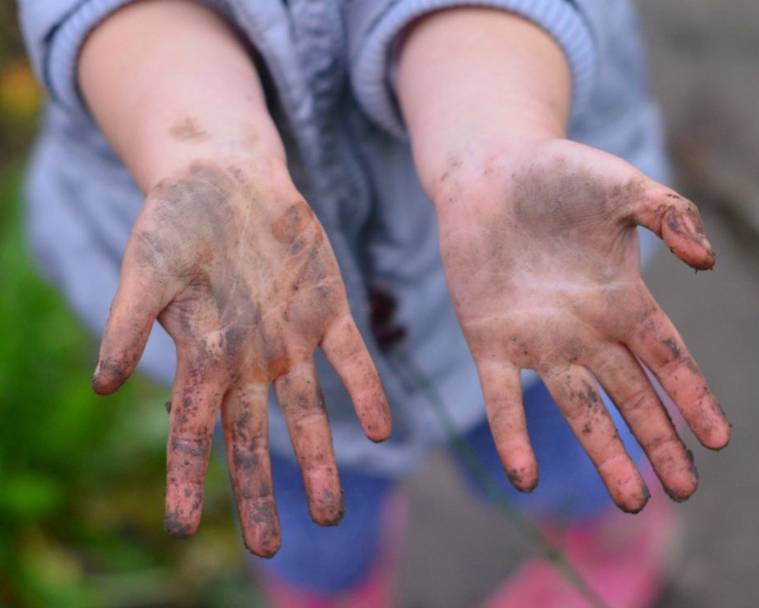 One of the Growing Family children with muddy hands