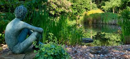 A statue on a rock in a garden