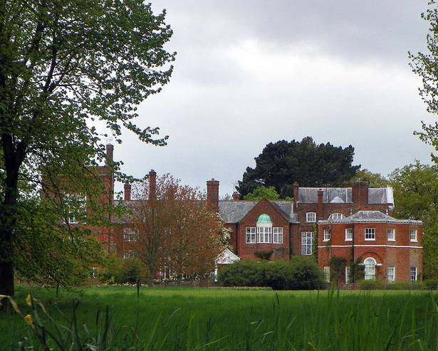 A large brick building with a grassy field with trees in the background