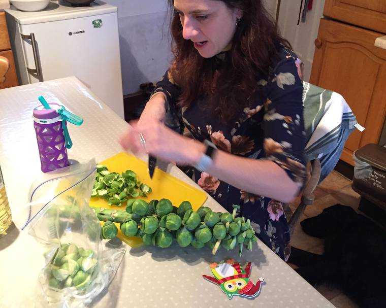 A person preparing Brussel sprouts at a table