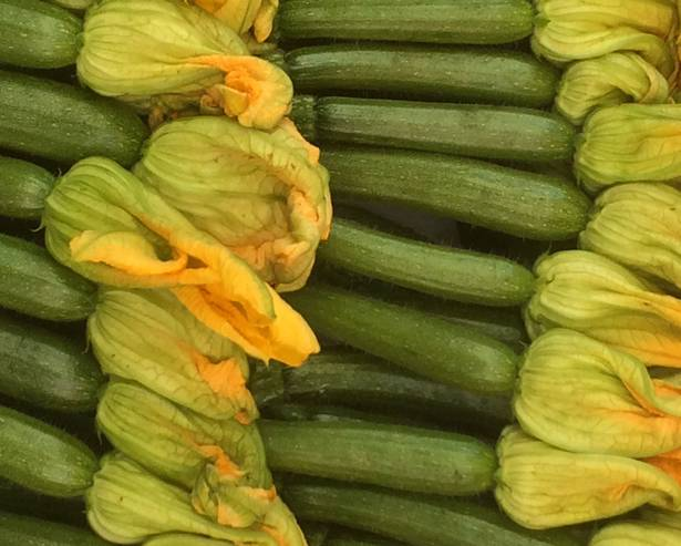 A pile of zucchini courgettes with flowers