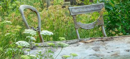 A rustic log bench in the summer at Quinton Old Rectory Garden