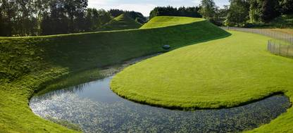 A body of water surrounded by green grass with The Golf Club at Harbor Shores in the background
