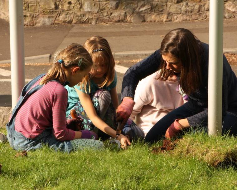 A lady and children planting flower bulbs