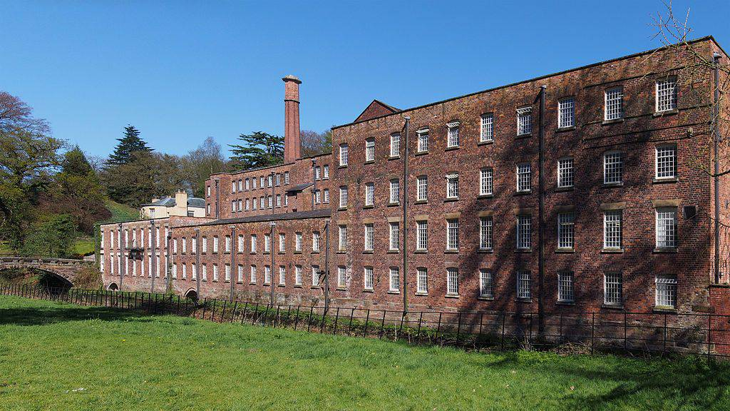 A large brick building with a grassy field with Quarry Bank Mill in the background
